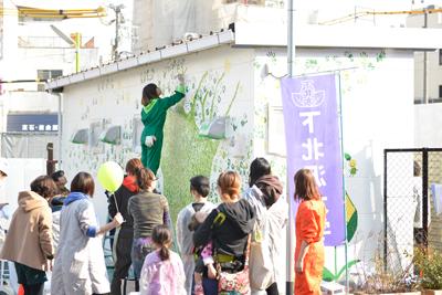 下北沢駅北口仮設トイレの壁面アートのデザインを行い、地元の方や子どもたちと一緒に手形で木の葉を描き、壁面アートを完成させました。
